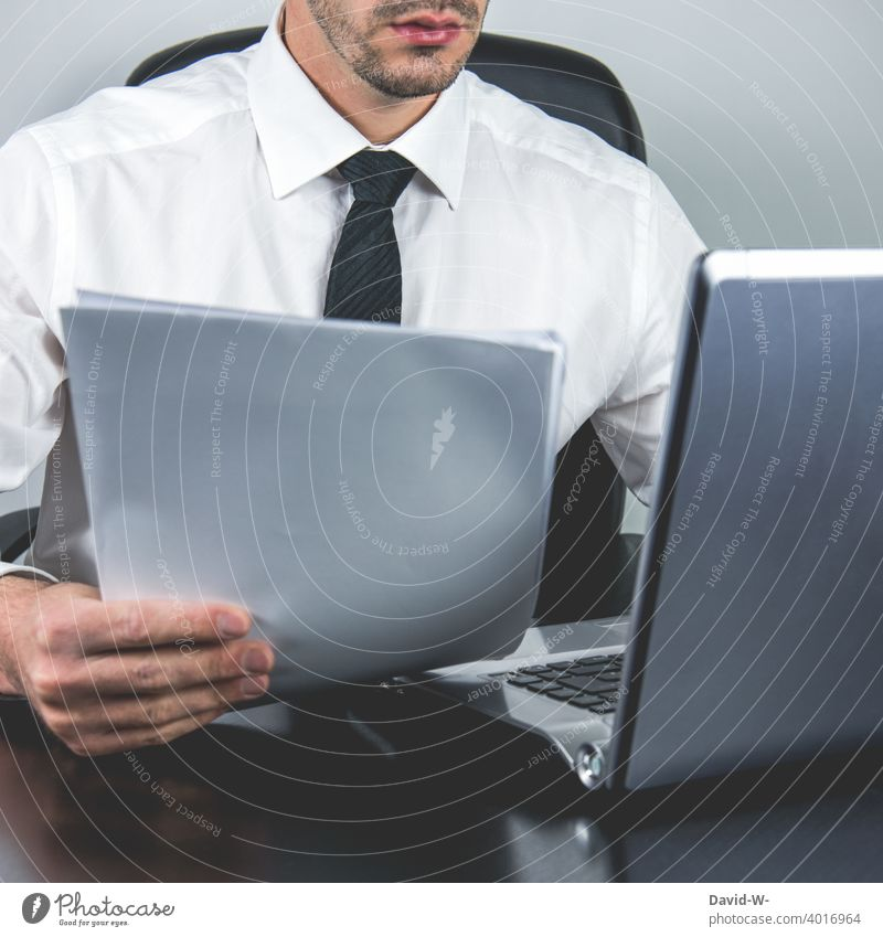 Man working on laptop and holding documents in hand home office Compter labour Accounts Notebook Workplace Office Online Suit