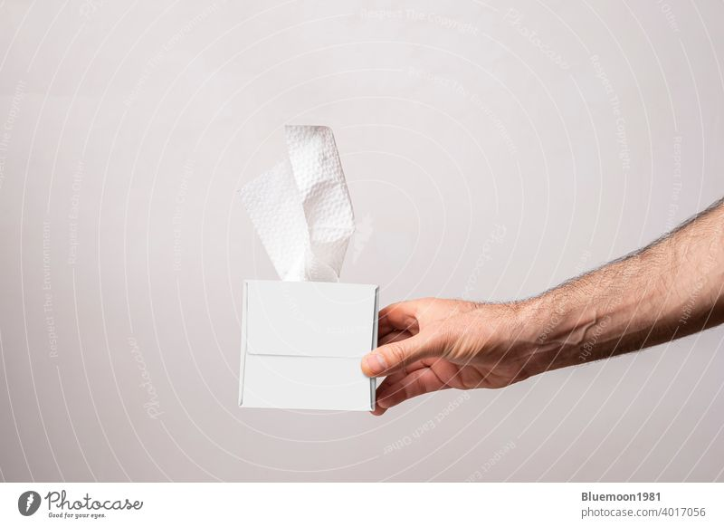 Male hand holding a cubical tissue box on white background mock-up editable change paper isolated napkin template facial product soft cardboard cleaner