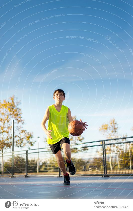 Cute boy in yellow shirt plays basketball on city playground. player teenage male training outside teenager bouncing sport outdoor competition game person