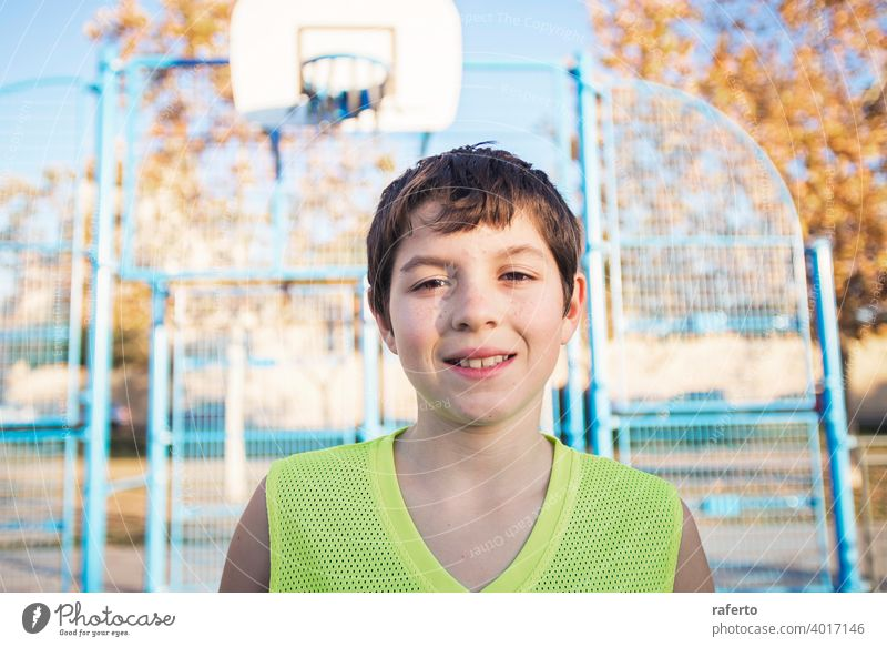 Portrait of a young teen male with sleeveless standing on a street basket court while smiling at camera basketball player real teenage youth boy fit happy game