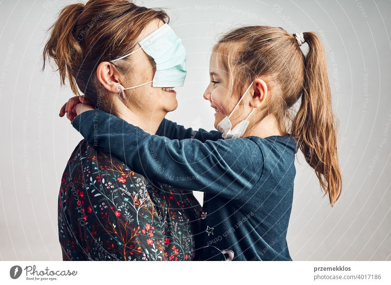 Little girl kissing her mother who has covered eyes with face mask for fun daughter child family woman love care together lifestyles protection healthy