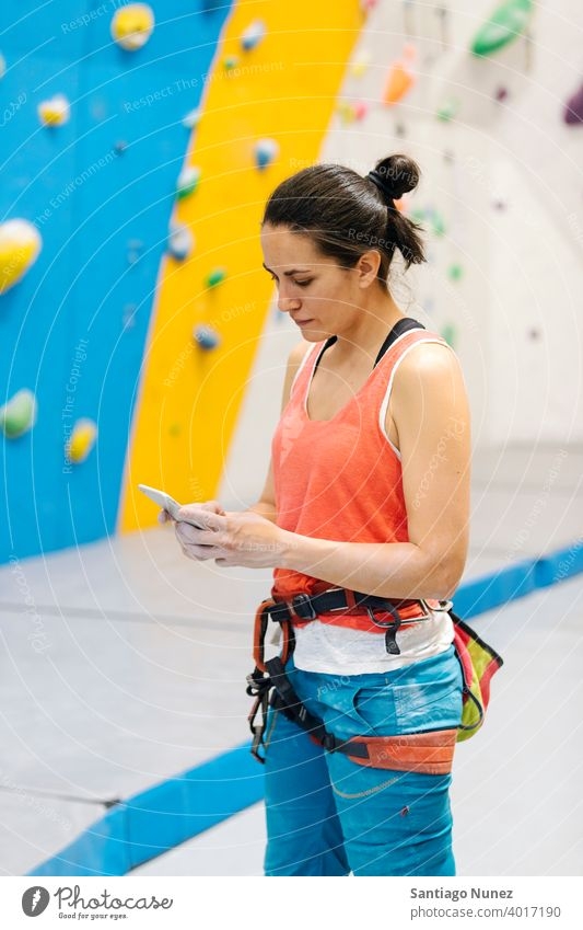Rock climber woman looking at smartphone. sport climbing training rock wall leisure athlete technology mobile phone cellphone activity fitness indoor exercise
