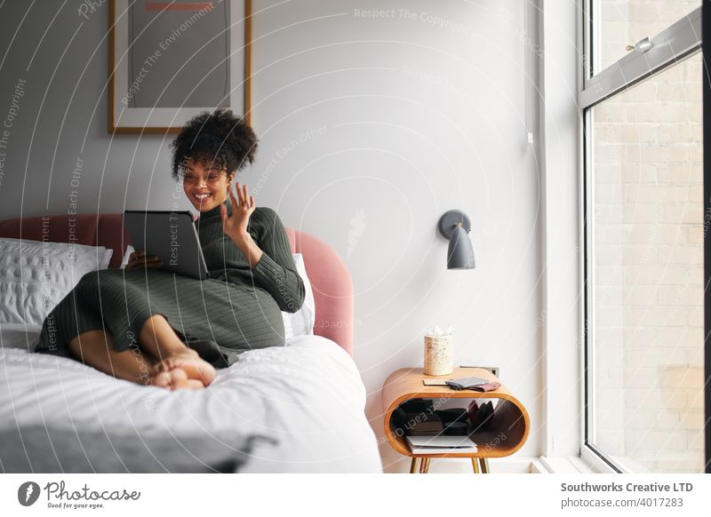 Woman Lying On Bed At Home Making Video Call On Digital Tablet woman at home digital tablet tablet computer video call video chat communication waving family