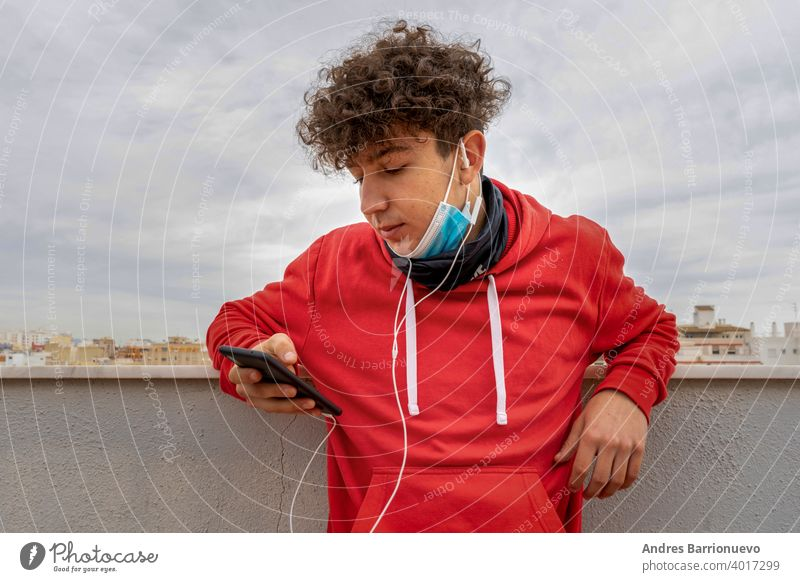 Young attractive man with curly hair dressed in a red sweatshirt using the mobile on the terrace of the house wearing a mask to protect himself from coronavirus