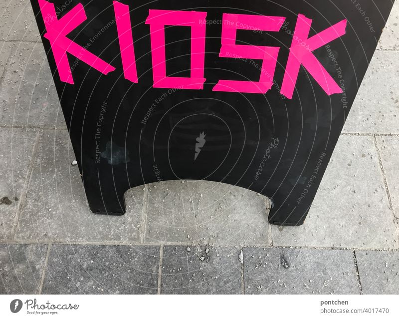 Kiosk is written in neon, pink, on a sign in front of a store. display Letters (alphabet) sale Sell Advertising Characters Signs and labeling Typography