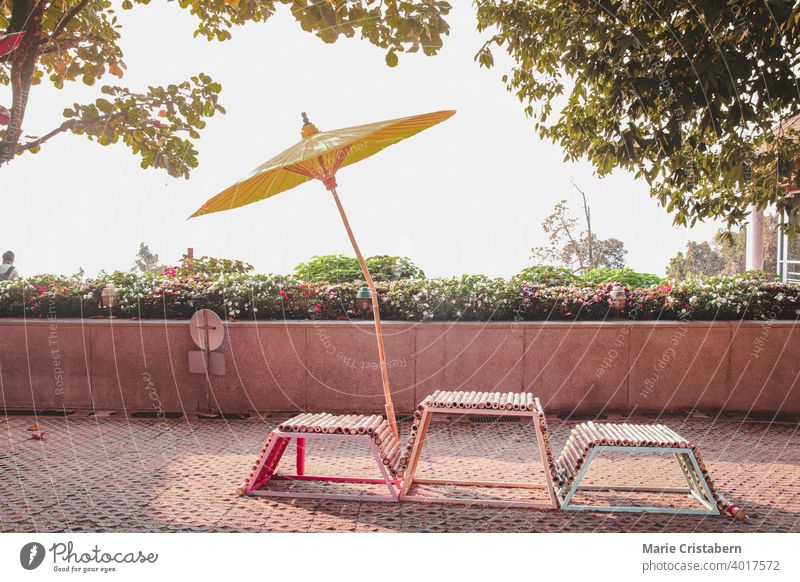 Chairs and a yellow Japanese umbrella on a summer day japanese umbrella japanese style oriental design asia chair garden tropical holiday vacation park outdoor