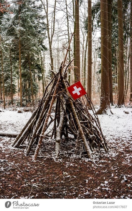 Tree branch made wooden tent play hut in the forest flying a small Swiss national flag snow winter swiss pyramid temporary built hut made of sticks season