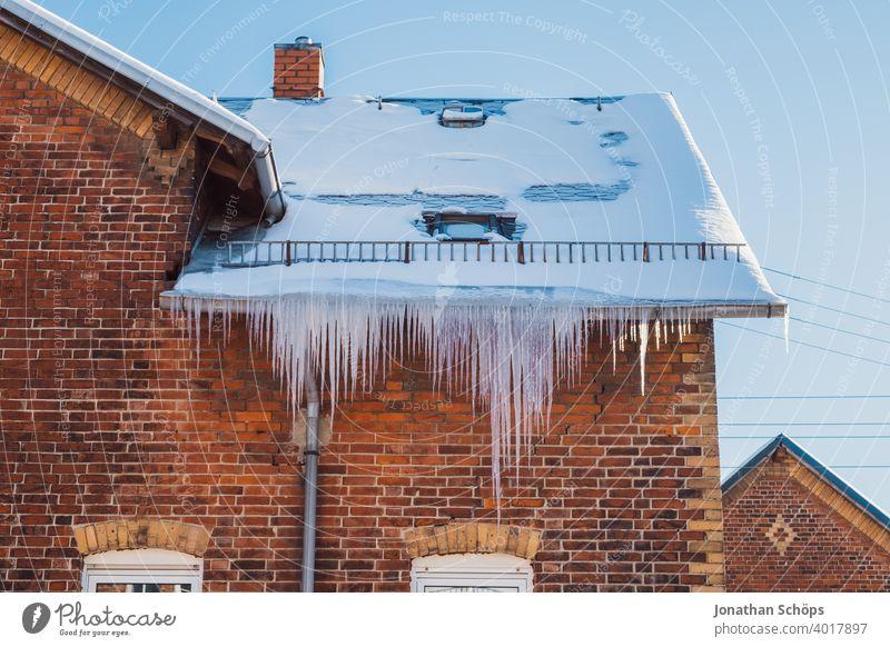 lange Eiszapfen an Dachrinne eines Backstein Haus im Winter bei eisiger Kälte und Sonne Architektur Backsteinhaus Backsteinhaussiedlung Dachkante Fallrohr
