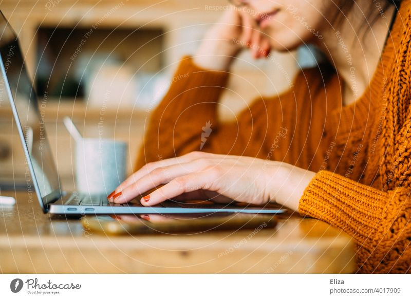 Young woman sitting at the table at home typing something on the notebook Notebook laptop Woman Online Surfing labour home office Home Office Typing Computer