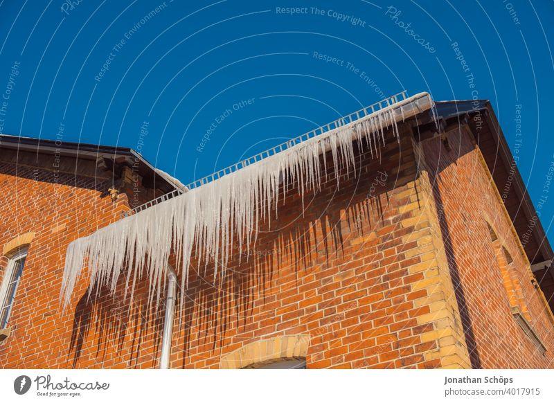 lange Eiszapfen an Dachrinne eines Backstein Haus im Winter bei eisiger Kälte und Sonne Architektur Backsteinhaus Backsteinhaussiedlung Dachkante