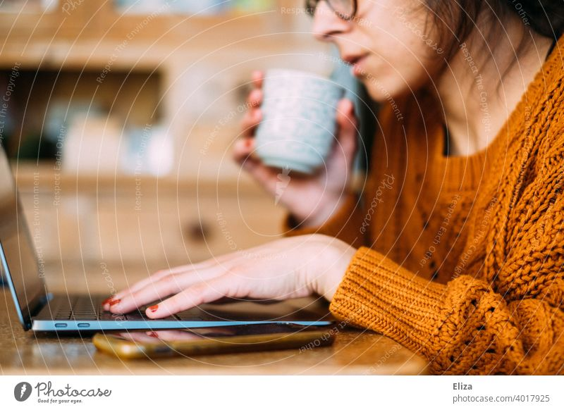 A woman sits at the table with coffee and laptop at home and works in the home office Home Office labour Coffee cup Notebook Computer Workplace Business