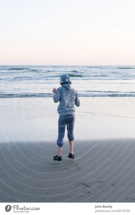 Child with Autism jumping in mid air out of joy; background is a beach with waves stop motion Freeze happy boy child childhood kid blue gray sand tide wet cool