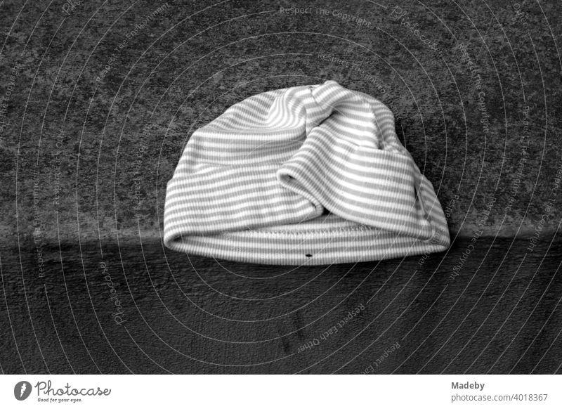Striped woollen cap in winter as a found object on a wall in winter in Oerlinghausen in the Teutoburg Forest in East Westphalia-Lippe Cap Woolen hat knitted cap