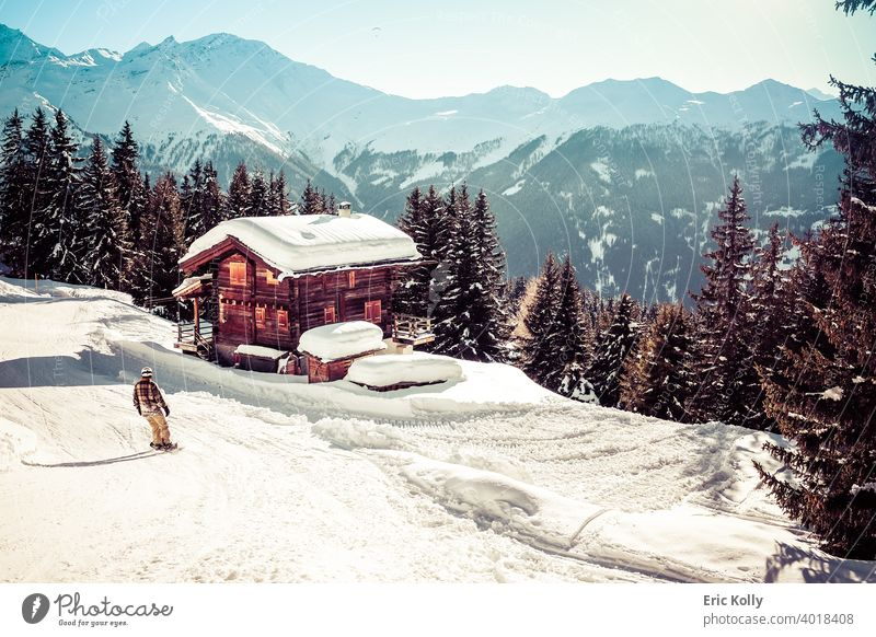 Ski resort of Verbier with a chalet covered by snow and a snowboarder in the foreground, shot in Verbier, Switzerland Winter Cold Exterior shot Snow White