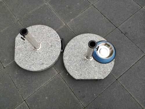 Round marble stands for parasols and round bowls for dogs on grey pavement at Hanauer Landstraße in the Ostend of Frankfurt am Main Umbrella stand Pillar