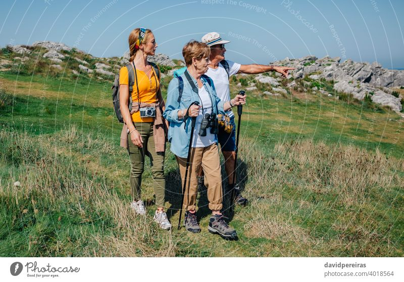 Family practicing trekking together outdoors hikers family countryside looking landscape nature journey summer recreation people hiking pointing backpack