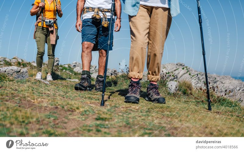 Three people practicing trekking outdoors unrecognizable group hikers mountain boots legs low section trekking sticks woman countryside landscape nature journey