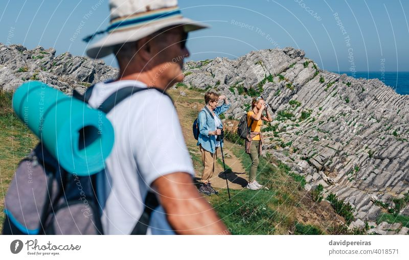 Family practicing trekking together outdoors hikers family camera taking picture landscape nature mountain countryside looking journey summer recreation people