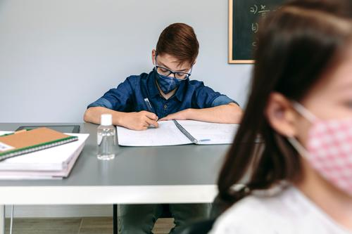 Boy with face mask writing at school boy student classroom new normal coronavirus safety people epidemic education health prevention young girl covid-19