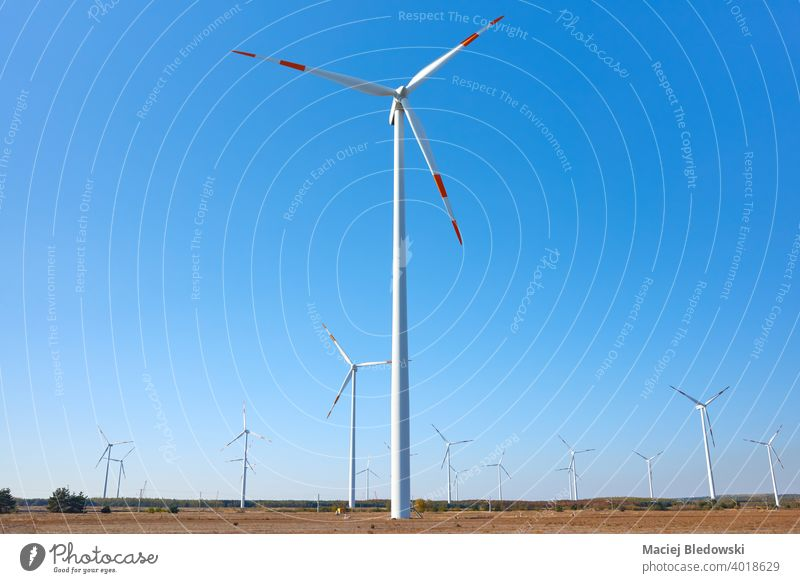 Picture of a wind turbine farm against the blue sky. windmill power green energy renewable electricity alternative environment generator equipment field