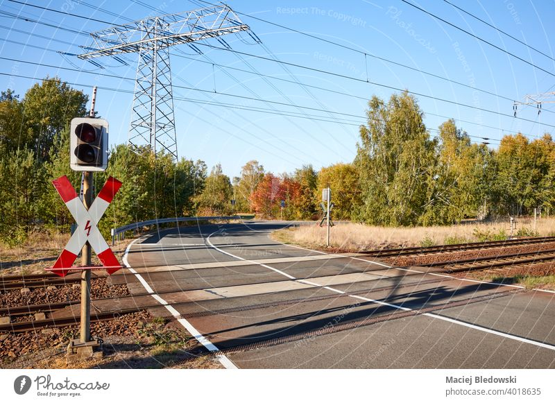 Rail crossing with high voltage power transmission line in background. transport level crossing rail crossing transportation railroad infrastructure signal