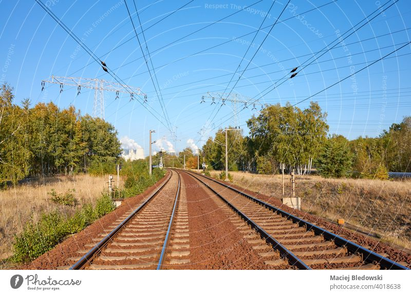 Railway with power station and high voltage power transmission line in background. travel railway track railroad transportation landscape industry forest
