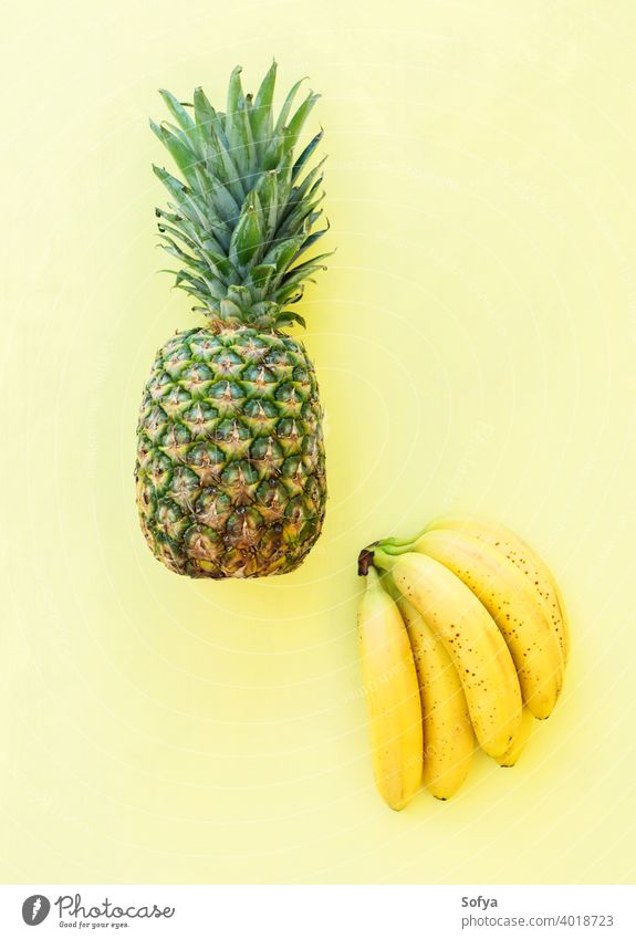 Whole pineaple banana fruit on yellow background, top view pineapple ananas bunch ripe fresh summer green organic texture close group stem sweet delicious food