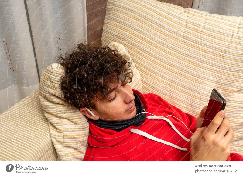 Young attractive man with curly hair dressed in a red sweatshirt using mobile in living room at home wearing a mask to protect himself from coronavirus