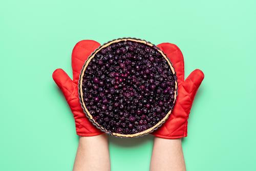 Blueberry pie fresh from the oven, top view. Woman holding blueberry pie with oven mitts above view american bake bakery baking bilberries blueberries tart
