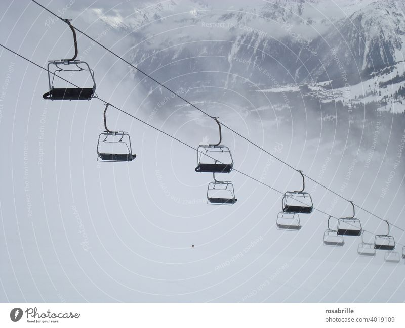 compliant | with corona rules - lonely standing chairlift in ski area | corona thoughts chair lift Skiing standstill Empty forsake sb./sth. Fog switched off
