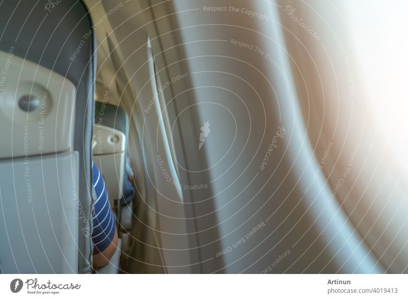 Rearview of airplane seat near plane window. Economy class airplane. Inside of commercial airline. Small space between passenger economy seat and window of airplane. Seat with armchair. Leather seat.