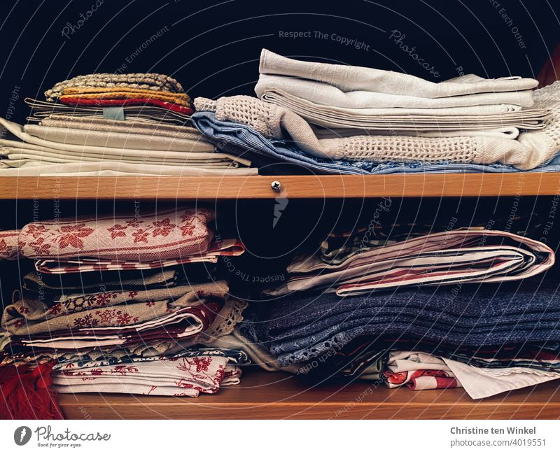 Tablecloths and doilies and old crocheted potholders, stacked more or less neatly in two closet compartments Doily Oven cloth Crocheted Substances