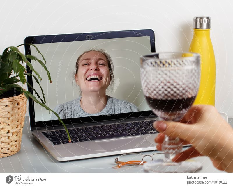Two friends drinking wine while having a video call glass women laptop isolation Social distancing videocall red wine smile laugh plant succulent grey person