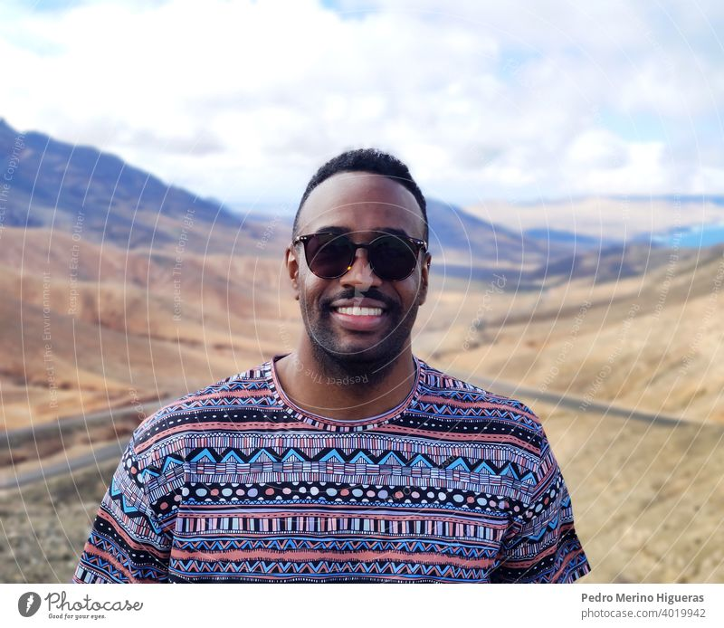 Black man portrait in a Fuerteventura viewpoint. isolated street beauty cheerful guy outdoors casual attire smiling person photogenic adult smile happy young