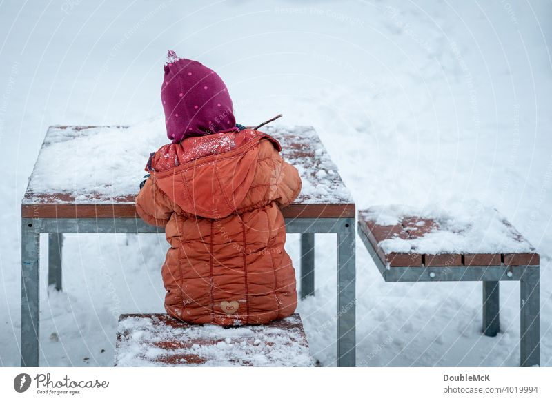 A child sits outside at the snowy table in the snow and plays Day Exterior shot naturally Life Joy Cold cold season Snow look away Winter chill 1 snow-covered