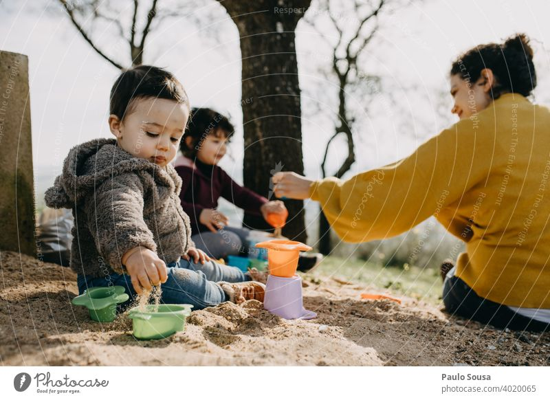 Child playing with mother and sister outdoors with sand childhood Family & Relations Infancy Childhood memory Colour photo Lifestyle Joy Caucasian Happiness