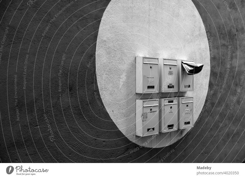 Mailboxes in a painted light circle on a dark facade in Offenbach am Main in Hesse, photographed in classic black and white Postman Letters Advertising