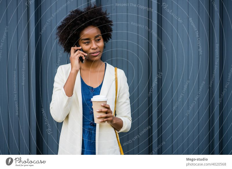 Business woman talking on the phone outdoors. afro business mobile modern style brunette gadget positive concept connection application sms texting