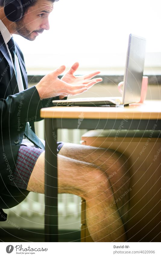 gesticulating man in shorts and jacket at laptop Gesture Notebook home office Discussion meeting conference Online zoom crazy Authentic reality concept pandemic