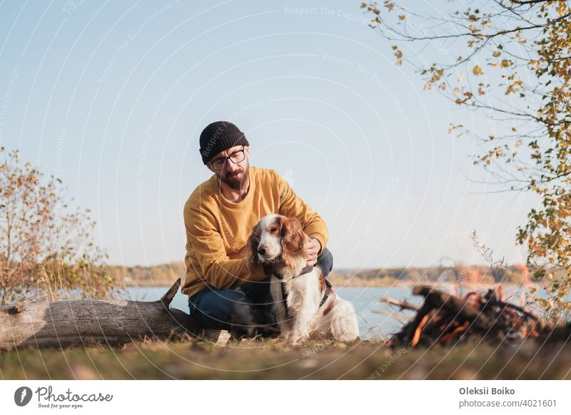 Man hugs his dog sitting by the lake. Active rest with pets, going on adventures, companionship: spaniel dog and his owner sit outdoors 25-35 years active