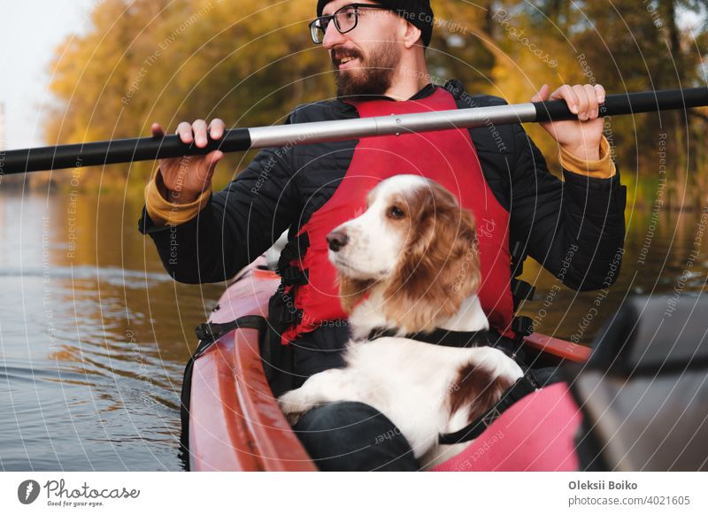 Happy man rowing a canoe with his spaniel dog, sunny autumn weather. Going kayak boating with dogs on the river, active pets, wholesome dog and owner on an adventure