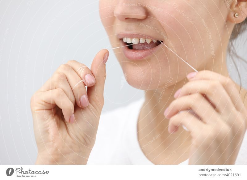 Oral hygiene and health care. Smiling woman use dental floss white healthy teeth. oral women mouth clean tooth young face smile fresh girl hand happy healthcare