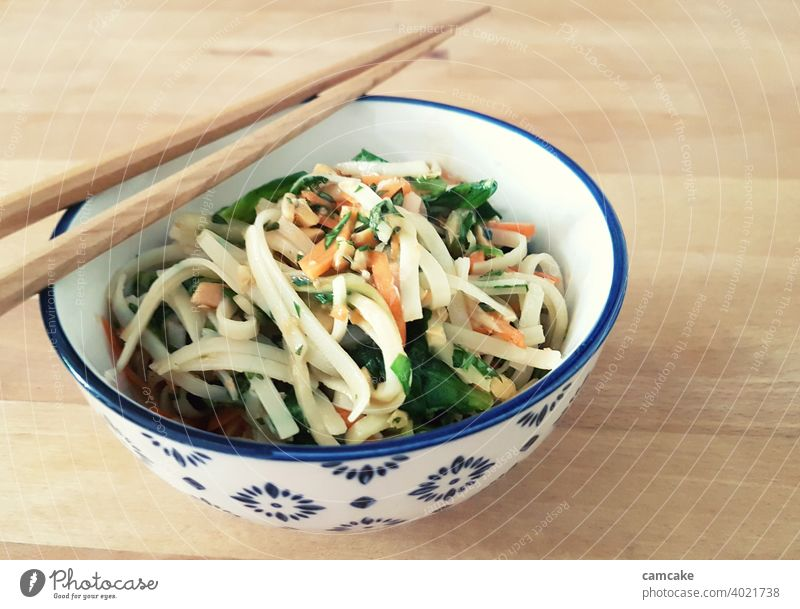 Pasta with vegetables and chopsticks in bowl Noodles Lettuce Asian Food Healthy Eating variegated Bowl Vegetable Pasta dish Ribbon noodle salubriously Delicious