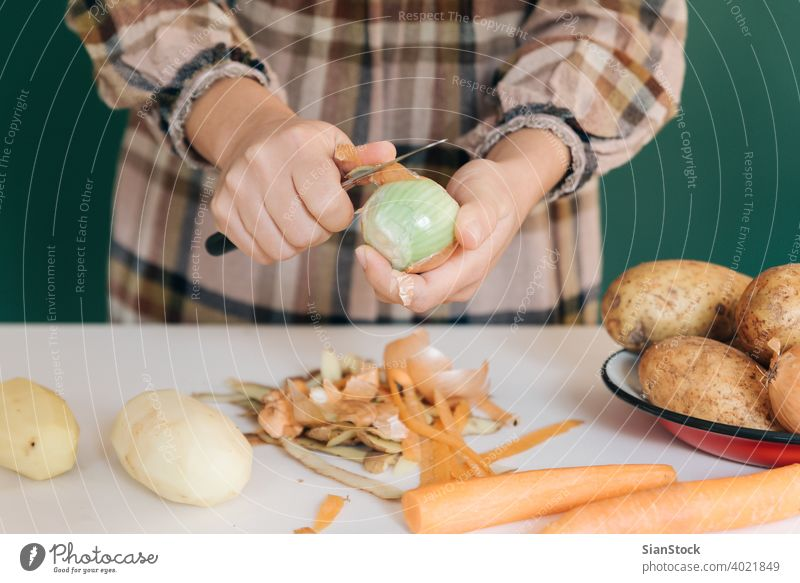 Woman peels off onions at her kitchen on white marble, to prepare her food. woman vegetable potatoes vegan home peel-off peeling carrots organic green cutting