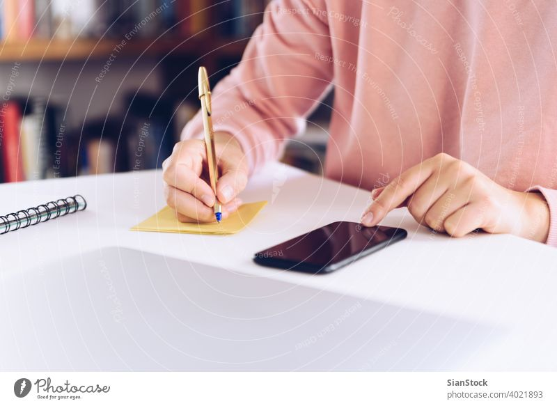 Young woman using mobile phone while working at home with laptop. business technology smart computer desk connection smartphone workplace freelancer message