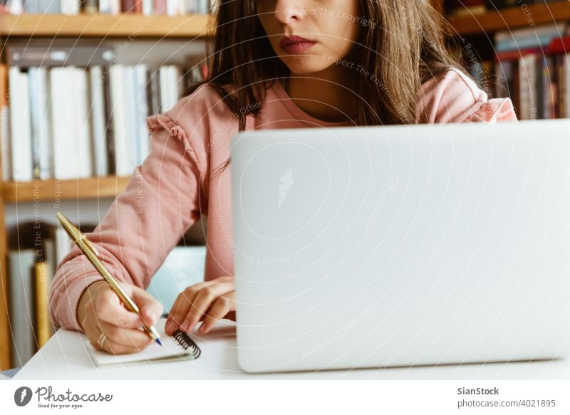 Young woman working on white marble desk at her home. young person hand table female notes library wooden pen business top background morning girl adult