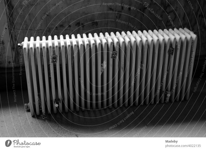Discarded traditional radiator in the dark cellar of a farmhouse in Rudersau near Rottenbuch in the district of Weilheim-Schongau in Upper Bavaria, photographed in classic black and white