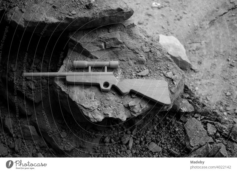 Toy rifle made of wood with telescopic sight on crumbling rock of an old farmhouse in Rudersau near Rottenbuch in the district of Weilheim-Schongau in Upper Bavaria, photographed in classic black and white