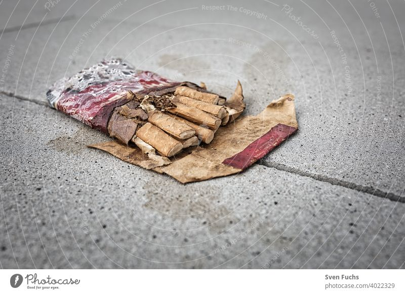 A crushed pack of cigarettes lies on the concrete floor Cigarette box Smoking quit smoking crumpled up Healthy