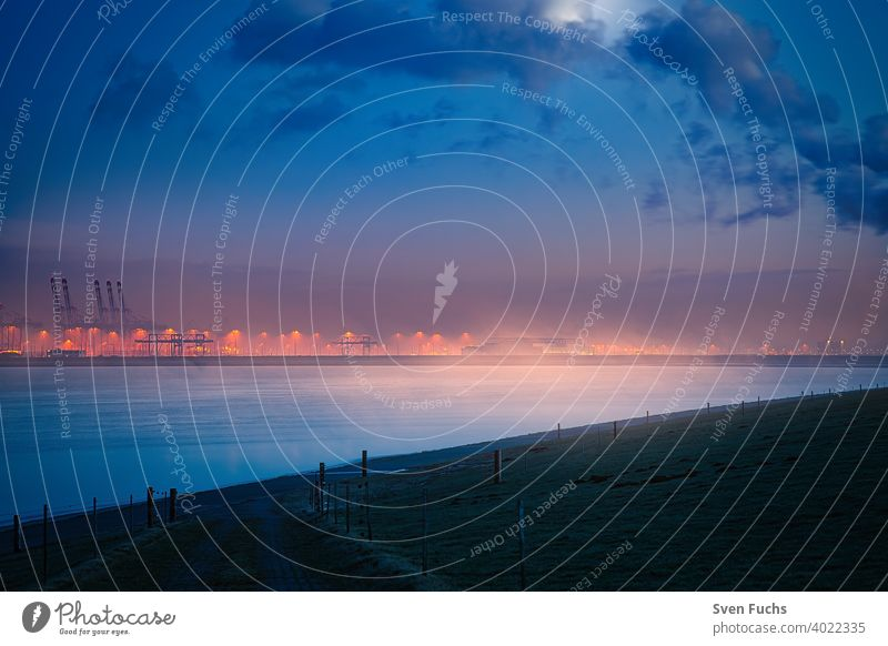 The Jade Weser Port at moonlight in a foggy atmosphere Harbour container port deepwater port Container cargo handling Maritime seafaring Twilight Fog blue hour